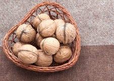 Orzech włoski w starym łozinowym koszu na burlap Zdjęcie Stock