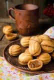 Orzecha włoskiego kształta ciastka z zgęszczonym mlekiem - Dulka De Leche w glinianym pucharze na drewnianym nieociosanym tle Sel Obrazy Royalty Free