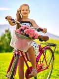Os às bolinhas brancos vestindo da menina da criança vestem passeios bicycle no parque Imagens de Stock Royalty Free