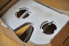 Os óculos de proteção da realidade virtual com as lentes óticas separaram do equipamento da cabeça do cartão na tabela de madeira Fotografia de Stock
