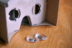Os óculos de proteção da realidade virtual com as lentes óticas separaram do equipamento da cabeça do cartão na tabela de madeira Imagens de Stock