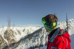 Os óculos de proteção do esqui do homem novo do retrato olham às montanhas Fotos de Stock