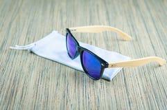 Os óculos de sol azuis elegantes em uma tampa de pano são de madeira na tabela fotografia de stock royalty free