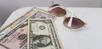 Os óculos de sol elegantes brancos colocam perto das contas americanas do papel dos dólares imagens de stock