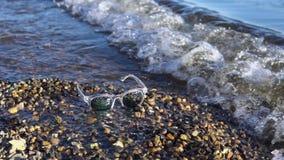 Os óculos de sol encontram-se em um Pebble Beach, ondas espirram na costa filme