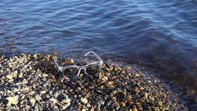 Os óculos de sol encontram-se em um Pebble Beach, ondas espirram na costa video estoque
