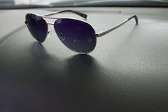 Os óculos de sol encontram-se no carro imagens de stock