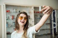 Os óculos de sol fazem-me mais sassy e elegante Morena consideravelmente caucasiano que toma o selfie na loja do ótico ao tentar  imagens de stock royalty free