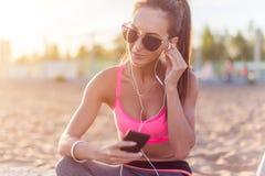 Os óculos de sol vestindo da mulher bonita do atleta da aptidão que descansam a música de escuta após dão certo o exercício na no Imagens de Stock Royalty Free