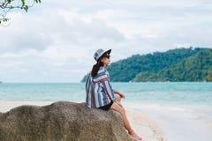 Os óculos de sol vestindo da mulher de Ásia que sentam-se na rocha e admiram o cenário Foto de Stock