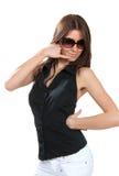 Os óculos de sol vestindo da mulher 'sexy' bonita da forma que mostram o telefone da chamada assinam Imagem de Stock Royalty Free