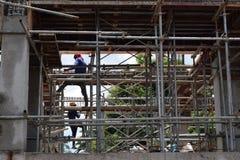 Os aço-homens da construção civil que trabalham através de uma malha do andaime conduzem no local de trabalho fotos de stock royalty free