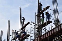 Os aço-homens filipinos da construção que trabalham partes de aço de junta da coluna a bordo do andaime conduzem no prédio imagens de stock royalty free