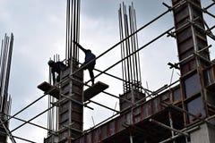 Os aço-homens filipinos da construção que trabalham partes de aço de junta da coluna a bordo do andaime conduzem no prédio Fotografia de Stock Royalty Free