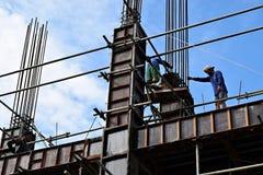 Os aço-homens filipinos da construção que trabalham partes de aço de junta da coluna a bordo do andaime conduzem no prédio Imagens de Stock