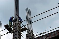 Os aço-homens filipinos da construção que trabalham partes de aço de junta da coluna a bordo do andaime conduzem no prédio Fotos de Stock Royalty Free