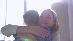 Os abraços da mãe, menina apressam-se nas mãos do mum e dão-se o abraço grande e beijam-se em casa contra a janela em raios do so