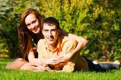 Os abraços novos felizes dos pares na grama Foto de Stock
