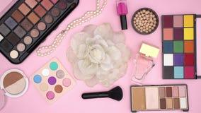 Os acessórios da mulher e para compor e os produtos de beleza no fundo cor-de-rosa vídeos de arquivo