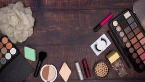 Os acessórios da mulher e para compor e os produtos de beleza no fundo de madeira filme