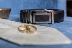 Os acessórios do noivo - laço, correia e alianças de casamento fotografia de stock
