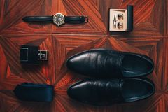 Os acessórios dos homens: relógio, laço, correia, botão de punho, opinião superior de sapatas do perfume foto de stock