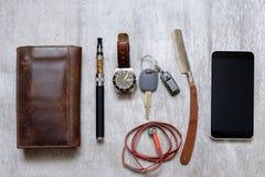Os acessórios, a opinião superior em uma carteira de madeira a bolsa do telefone, a lâmina e o e-cigarro dos homens Fotos de Stock