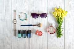 Os acessórios, os cosméticos e os wildflowers das mulheres Imagens de Stock