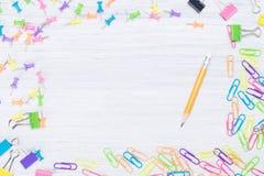 Os acessórios pequenos do escritório para unir de papel encontram-se em torno do lápis foto de stock royalty free