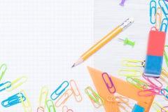 Os acessórios pequenos do escritório para unir o papel e um lápis encontram-se no canto da tabela imagem de stock royalty free