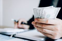 Os acionistas estão calculando em custos de investimento da calculadora e estão guardando notas de dinheiro à disposição imagens de stock