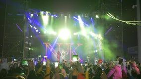 Os admiradores da multidão com telefones celulares nas mãos deleitam a música ao vivo no festival da rocha no holofote brilhante  filme