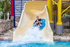 Os adolescentes asiáticos que apreciam seu slider da água montam-nos em uma água Fotos de Stock