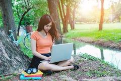 Os adolescentes asiáticos sentam o uso recreacional do portátil Fotografia de Stock Royalty Free