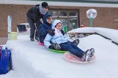 Os adolescentes asiáticos têm o divertimento que desliza para baixo na neve com neve plástica Imagem de Stock