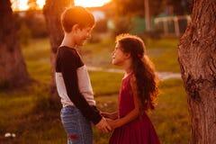 Os adolescentes da menina do menino estão mantendo as mãos romances Fotos de Stock