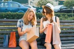 Os adolescentes das meninas sentam-se no banco na cidade e no olhar em compras em uns sacos de compras fotos de stock royalty free