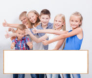 Os adolescentes de sorriso que mostram o sinal aprovado no branco Fotos de Stock