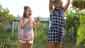 Os adolescentes estão saltando no sol sob córregos da água Conceito feliz do feriado, férias de verão video estoque