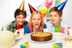 Os adolescentes felizes comemoram velas do sopro da menina do aniversário foto de stock