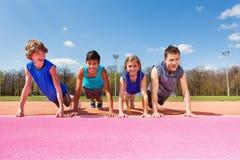 Os adolescentes felizes que fazem a flexão de braço exercitam exterior Fotos de Stock Royalty Free
