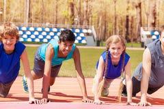 Os adolescentes felizes que fazem a flexão de braço exercitam na trilha Fotos de Stock