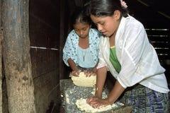 Os adolescentes guatemaltecos amassam o milho à terra na massa Foto de Stock Royalty Free