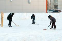 Os adolescentes jogam o hóquei em uma pista de patinagem doméstica Tyumen, Rússia Fotos de Stock