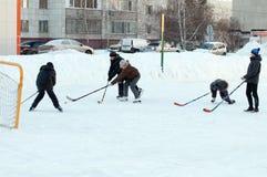 Os adolescentes jogam o hóquei em uma pista de patinagem doméstica Tyumen, Rússia Fotografia de Stock Royalty Free
