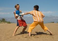 Os adolescentes na areia do mar imagens de stock