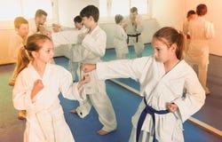 Os adolescentes que praticam o karaté novo movem-se em pares na classe Imagem de Stock Royalty Free