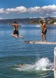 Os adolescentes que saltam fora da placa de mergulho Fotografia de Stock