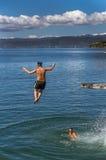 Os adolescentes que saltam fora da placa de mergulho Imagens de Stock