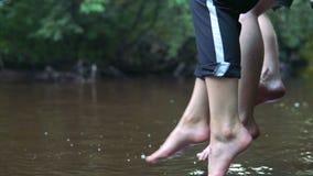 Os adolescentes relaxam pelo rio que senta-se na borda de um molhe de madeira filme